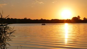 Fishermen sail in a boat on the lake. At sunset stock video
