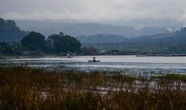 Fishermen on boats are fishing on the background of trees royalty free stock images