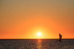 Fishermen in a sailboat at a beautiful warm orange glow sunset Royalty Free Stock Images