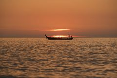 Fishermen sailing in the sea during sunset royalty free stock images