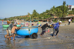 Fishermen after the sea dragged round plastic boat ashore. The fishing harbor of Mui Ne, Vietnam Stock Photo