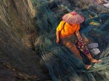 Fishermen sewing fishing net. Borneo, Sarawak 5 august 2018, Sadilo Mataiem, 67, sewing a fishing net in Kampung Bako, Kuching. Many of the villagers are royalty free stock images