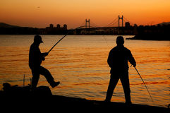 Fishermen silhouette on the beach. At colorful sunset Stock Photos