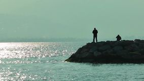 Fishermen silhouette on the Rocks Royalty Free Stock Photos