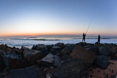 Fishermen Silhouetted Ocean Beach Sunrise. Fishing fishermen silhouetted early dawn ocean horizon sunrise beach Royalty Free Stock Images
