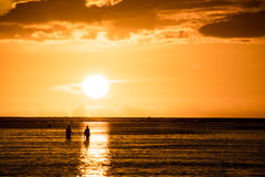Fishermen silhouettes with sunset background Royalty Free Stock Photo