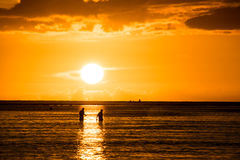 Fishermen silhouettes with sunset background Stock Photo