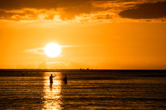 Fishermen silhouettes with sunset background Stock Photography