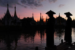 Fishermen silhouettes at sunset and pagodas Royalty Free Stock Photo