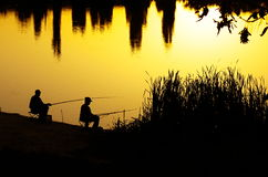 Fishermen silhouettes at sunset Stock Photography