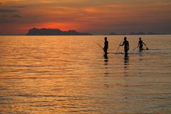 Fishermen silhouetting against sunset. Fishermen catching dinner at a remote coastline in southern Thailand Stock Photo