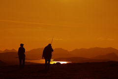 Fishermen silhouttes. Silhouettes of two fishermen walking. Photo taken in the wilderness of Swedish Lapland stock photo