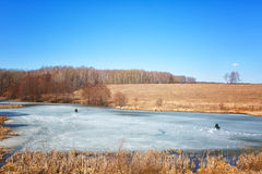 Fishermen sit on the ice pond Stock Image
