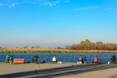Fishermen sit on the pier near the river and fish royalty free stock image