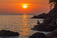 Fishermen in sunset rays. Fishermen sitting on the rocks in the rays of the setting sun Stock Photos