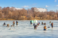 Fishermen sitting and walking on ice Royalty Free Stock Photography