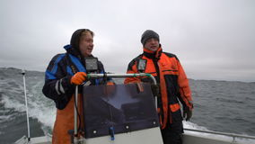 Fishermen on a small boat out to sea to fish. Two brave fishermen on a small boat out to sea to fish stock video footage