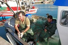 Fishermen sorting catch, Spain. Stock Images