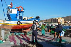 Fishermen sorting nets, Spain. Royalty Free Stock Photography
