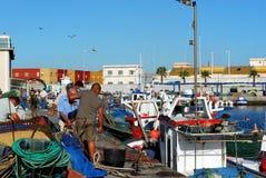 Fishermen sorting nets, Spain. Royalty Free Stock Images