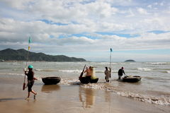 Fishermen in the South China sea off the Vietnamese coast near the city of Nha Trang. The fishermen come ashore after fishing and carrying gear of small round Stock Photography