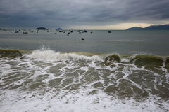 Fishermen in the South China sea off the Vietnamese coast near the city of Nha Trang. Fishing boats on a cloudy January morning in large numbers near the coast Royalty Free Stock Photography