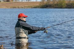 Fishermen spin fishing. Using chest waders to stay dry Royalty Free Stock Photos
