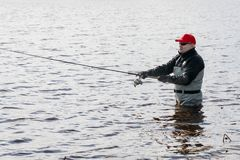 Fishermen spin fishing using chest waders. To stay dry Royalty Free Stock Images