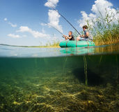 Fishermen. Split shot of two fishermen in the boat in reed's thicket and underwater view of the bottom Royalty Free Stock Photo