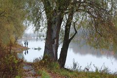 Fishermen stand by the water of a forest lake in autumn. Royalty Free Stock Photography