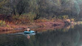 Fishermen stand by the water of a forest lake in autumn. Stock Images