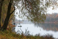 Fishermen stand by the water of a forest lake in autumn. Stock Photos