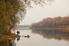 Fishermen stand by the water of a forest lake in autumn. Stock Photography