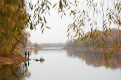 Fishermen stand by the water of a forest lake in autumn. Royalty Free Stock Photos