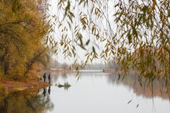 Fishermen stand by the water of a forest lake in autumn. Stock Photo