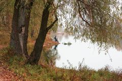 Fishermen stand by the water of a forest lake in autumn. Royalty Free Stock Photo