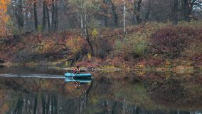 Fishermen stand by the water of a forest lake in autumn. Royalty Free Stock Image