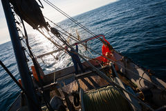 Fishermen standing at the stern of small fishing vessel Stock Image