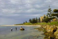 Fishermen standing in water at seaside Stock Image