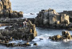 Fishermen on stone cliff. Surrounded by waves of  Japanese sea near Tojinbo. Tōjinbō 東尋坊  is a series of cliffs on the Sea of Japan in stock photo