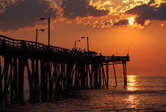 Fishermen at sunrise on a fishing pier. Early-morning anglers are silhouetted against the rising sun on a fishing pier in Nags Head, North Carolina Stock Image