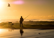 Fishermen at Sunrise. Fishermen with fishing rod at sunrise on beach Stock Image