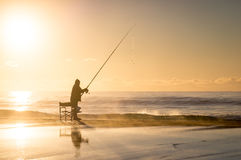 Fishermen at Sunrise. Fishermen with fishing rod at sunrise on beach Stock Photo