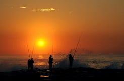 Fishermen at sunrise. Fishermen forming a silhouette against the orange sunrise Stock Photography