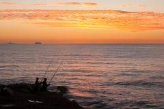 Fishermen at sunrise. Landscape of two men fishing at sunrise, at arpoador, Rio de Janeiro, Brazil Royalty Free Stock Image