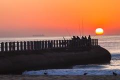 Fishermen Sunrise Ocean Jetty. Fishermen fishing dawn on pier jetty as sun rises over the ocean horizon Royalty Free Stock Images