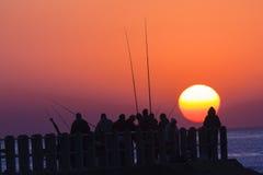 Fishermen Sunrise Ocean Jetty. Fishermen fishing dawn on pier jetty and sun rises over the ocean horizon Royalty Free Stock Image