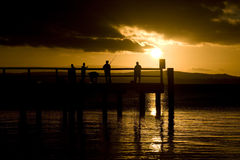 Fishermen at sunset. Group of people fishing on pier at sunset Royalty Free Stock Photography
