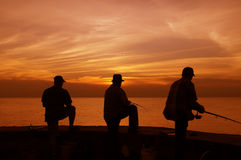 Fishermen at sunset. Silhouette of three fishermen with beautiful sunset background Stock Photography