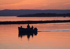 Fishermen at sunset. Fishermen coming home at sunset after a day on the lake Stock Photos